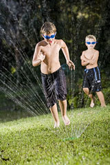 two boys cooling off in a lawn sprinkler
