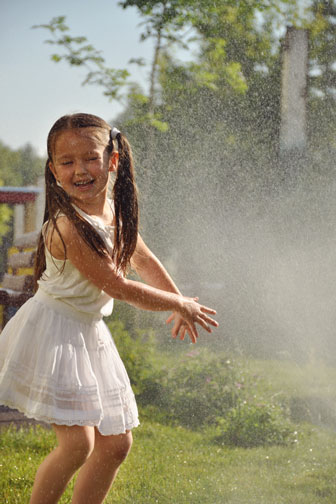 little girl cooling off in spray from a lawn sprinkler